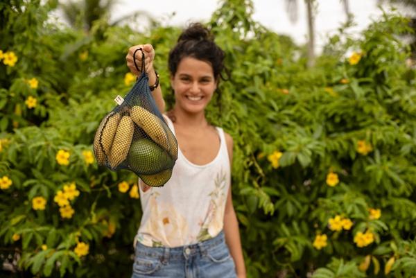 Jovem sorrindo ao segurar um saquinho feito de redes para comprar produtos, grãos, frutas e verduras a granel. O saquinho é feito de redes de pescas descartadas. Estímulo ao consumo consciente.
