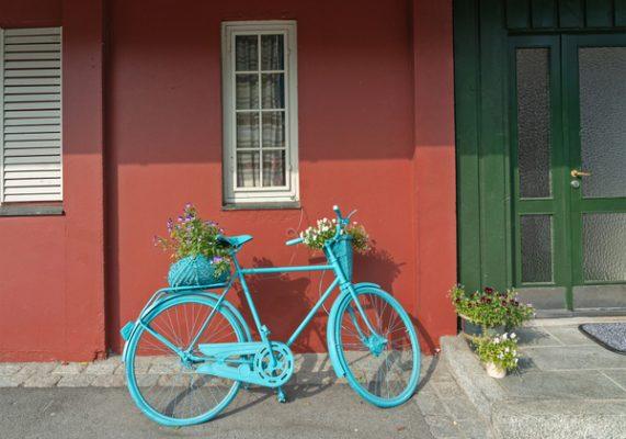 Bicicleta perto de casa rural tradicional escandinava. Utilizada como vaso de plantas. Decoração para jardinagem. Conheça os benefícios de andar de bicicleta!