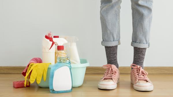 Vista frontal das pernas com soluções de limpeza e luva. Saiba mais sobre como a água sanitária pode gerar intoxicação por cloro.