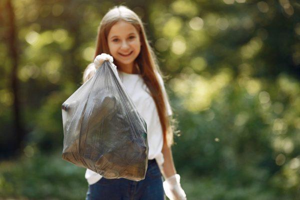 Para todes verem: Menina coleta lixo em sacos de lixo no parque. Confira o texto e saiba mais sobre a história do plástico!
