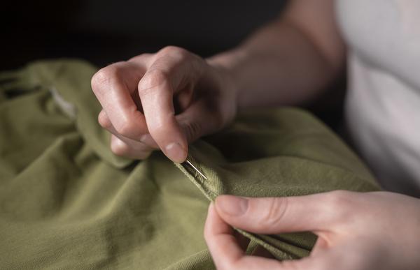 moda sustentável: Mãos femininas com agulha e linha para consertar roupas, close-up.