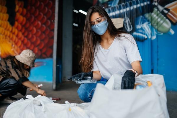 Jovem classificando o lixo para reciclagem. Saiba mais sobre a parceria Positiv.a + eureciclo!
